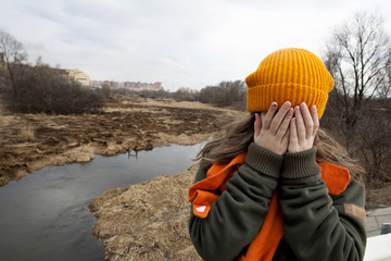 Sad teenager in orange knitten hat  closed her face by hands