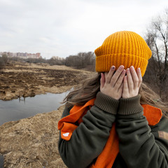 Sad teenager in orange knitted hat  closed her face by hands