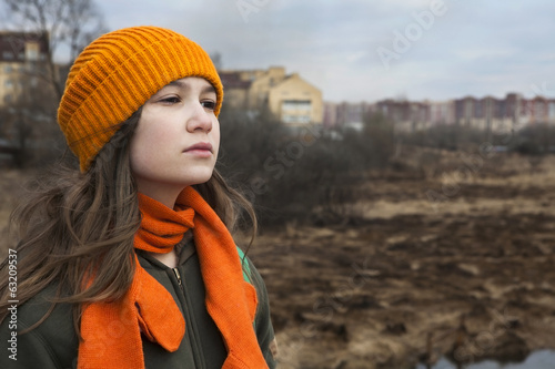 Pensive Teenager in orange knitten hat near scorched field.