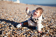 baby girl in the coat playing in the pebbles on the beach