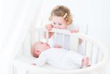 Fototapety Cute newborn baby boy watching his toddler sister