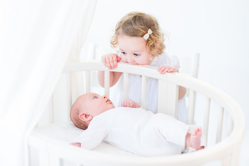 Cute newborn baby boy watching his toddler sister