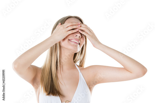 Woman hiding her eyes with hands and smiling isolated on white b