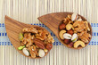 Selection of mixed nuts in wooden bowls on bamboo mat