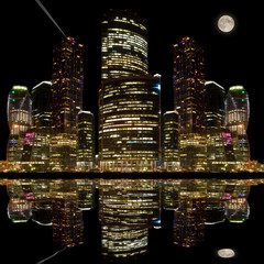 Night city view with its reflection in the water of the river.
