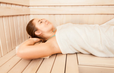 Portrait of beautiful woman lying on bench at sauna