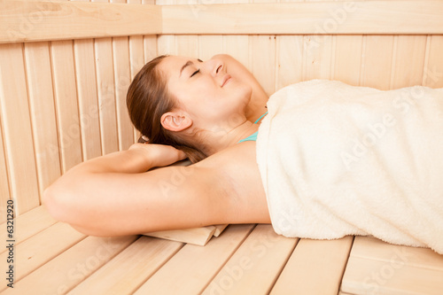 portrait of brunette woman covered in towel lying at sauna