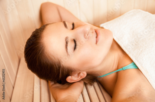 portrait of brunette woman lying with closed eyes at sauna