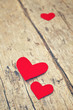 Red paper hearts on grunge wooden background