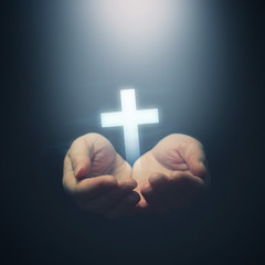 Open hands holding Christianity cross
