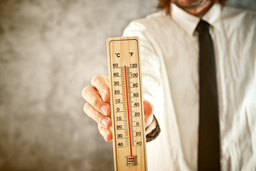 Businessman holding thermometer, measuring high temperatures