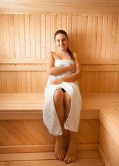 Beautiful smiling woman relaxing at finnish sauna