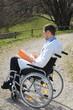 Arzt im Rollstuhl mit Unterlagen im Park 2