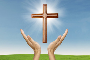 Male hands praying with a wooden cross