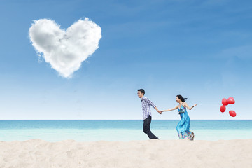 Running couple at beach under heart cloud