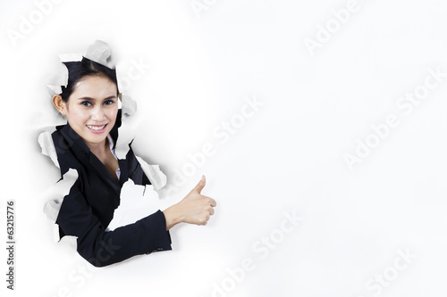 Satisfied businesswoman showing thumb-up