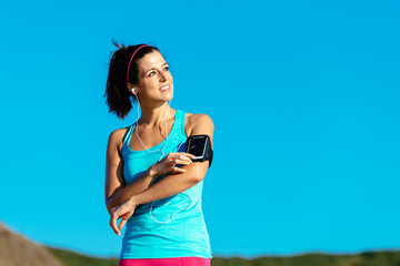 Sporty woman with smartphone armband and earphones