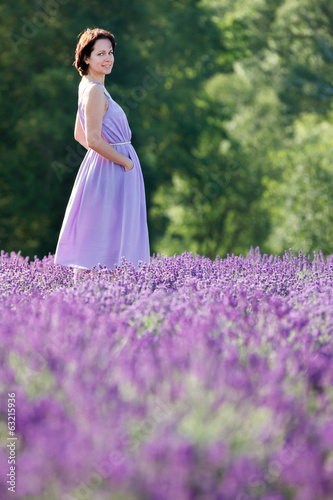 Beautiful woman relaxing in lavender field
