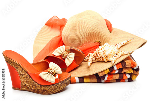 Beach hat, towel, stylish woman shoes and a seashell
