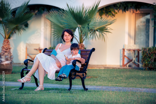Happy mother and son sitting outdoors