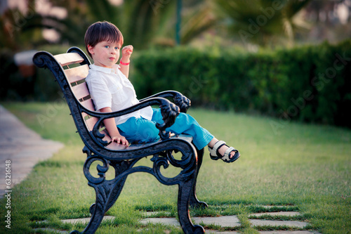 Three years old boy sitting on bench in park