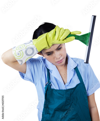 Tired maid holding cleaning tool
