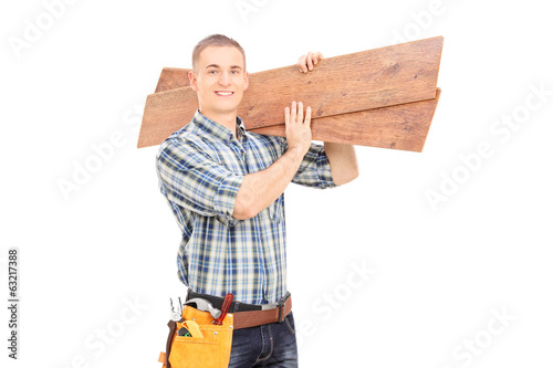 Male carpenter carrying planks over his shoulder