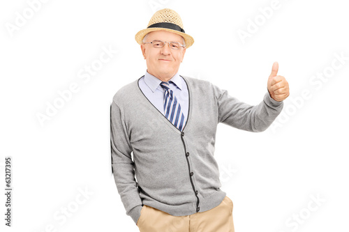 Man leaning against a wall and giving a thumb up