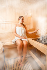 Photo of woman sitting in steamed sauna next to oven