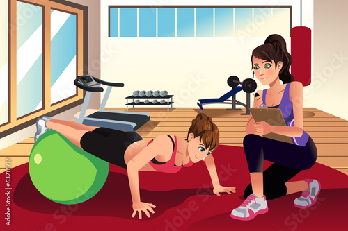 Female personal trainer training a woman in the gym