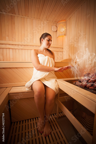 Photo of beautiful woman sitting next to oven at sauna