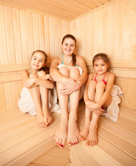 Photo of two little girls relaxing in sauna with mother