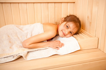 Closeup portrait of little girl lying on towel at sauna
