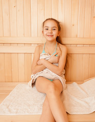 Portrait of smiling little girl sitting on bench at sauna
