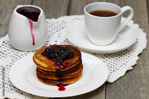Pancakes and jam on white dishware