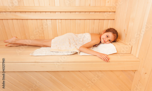 Portrait of cute little girl relaxing on bench at sauna