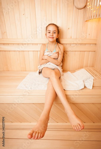 Photo of young girl with long legs sitting on towel at sauna