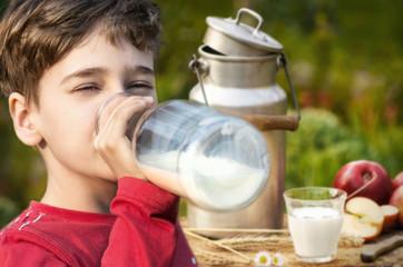 Junge trinkt frische Milch im Freien