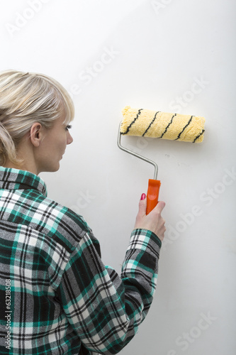 Woman - paints a wall with the painting roller