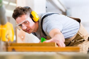 Tischler oder Schreiner beim sägen in Tischlerei