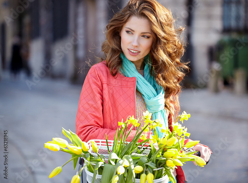 sensual brunette girl sitting on bicycle with some spring flower