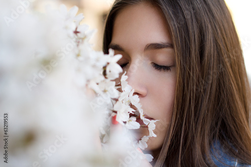 Young woman smelling cherry tree