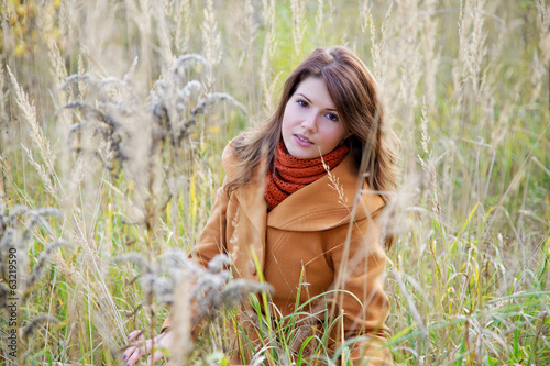 The girl among a high autumn grass