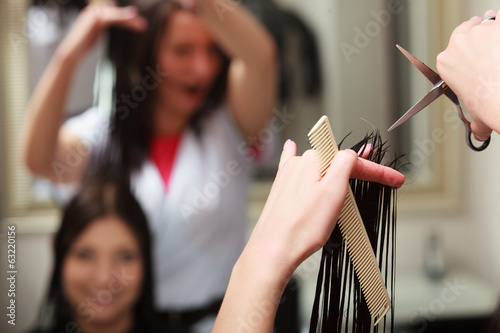 Hairstylist cutting hair woman in hairdressing beauty salon