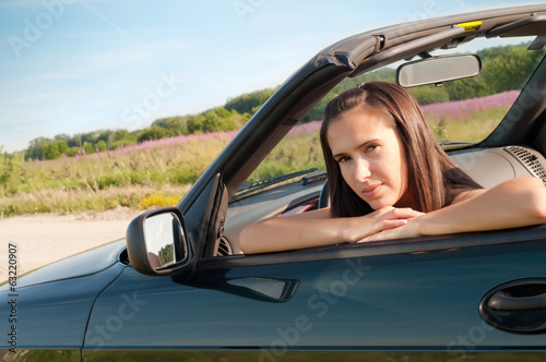 Beautiful brunette female sitting in car