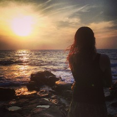 girl looks out to sea at sunset