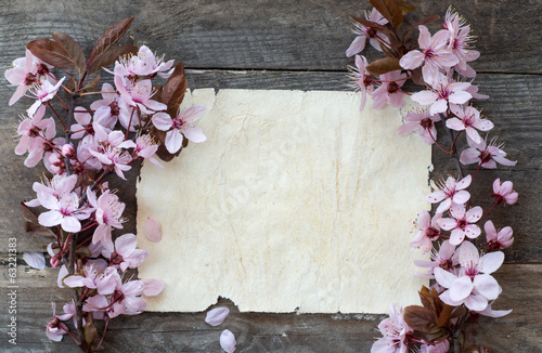 Spring blossom witth papr sheet on wood background