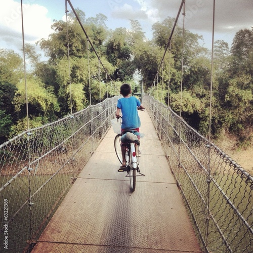 boy cycles over suspension rodge near battambang