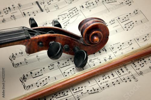 Staande foto Muziekwinkel Violin stick, peg box and scroll, on music sheet. Vintage style.