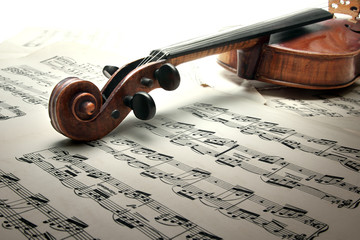 Detail of old scratched violin with sheet music. Vintage style.